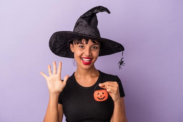 Młoda kobieta rasy mieszanej przebrana za wiedźmę na białym tle na fioletowym tle uśmiechając się wesoło pokazując numer pięć palcami.