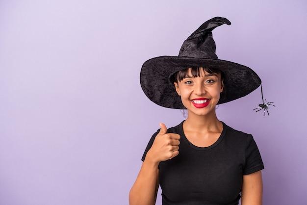 Młoda kobieta rasy mieszanej przebrana za wiedźmę na fioletowym tle uśmiechnięta i unosząca kciuk w górę
