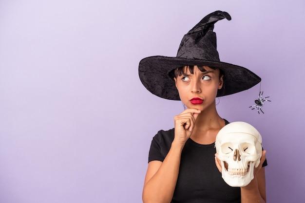 Młoda kobieta rasy mieszanej przebrana za wiedźmę trzymającą czaszkę na fioletowym tle, patrzącą w bok z powątpiewaniem i sceptycznym wyrazem twarzy.