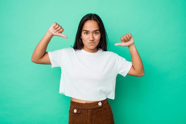 Młoda kobieta rasy mieszanej rasy na białym tle czuje się dumna i pewna siebie, przykład do naśladowania.