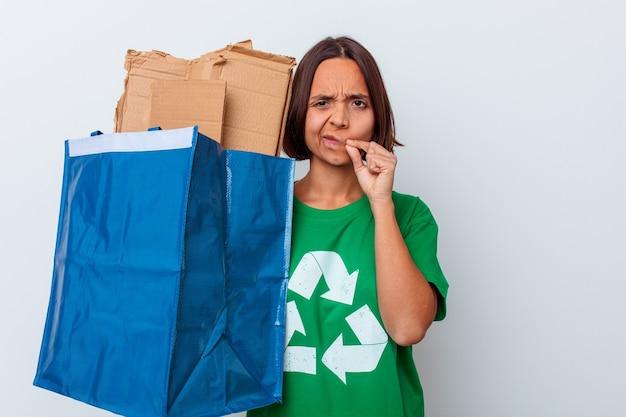 Młoda kobieta rasy mieszanej recyklingu kartonu na białym tle na białej ścianie z palcami na ustach, zachowując tajemnicę.