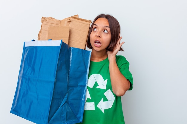 Młoda kobieta rasy mieszanej recyklingu kartonu na białym tle na białym tle próbuje słuchać plotek.