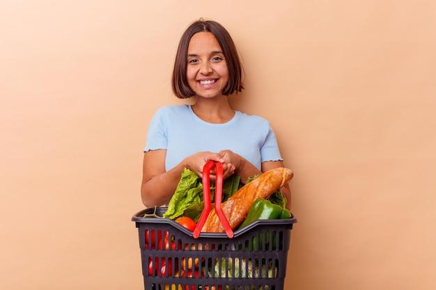 Młoda kobieta rasy mieszanej robi zakupy na białym tle na beżowej ścianie