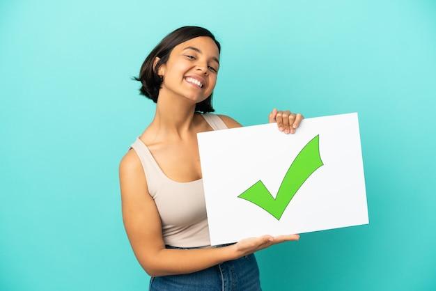 Młoda kobieta rasy mieszanej samodzielnie na niebieskim tle trzyma tabliczkę z tekstem ikona znacznika wyboru zielony z happy wypowiedzi