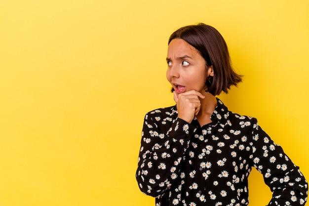 Młoda kobieta rasy mieszanej samodzielnie na żółtym tle dotykając tyłu głowy, myśląc i dokonując wyboru.