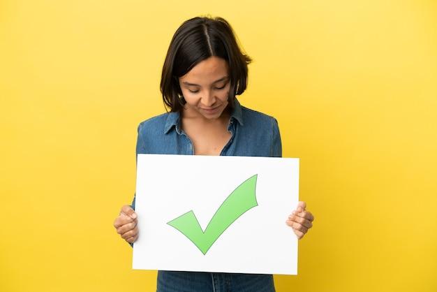 Młoda kobieta rasy mieszanej samodzielnie na żółtym tle trzymając plakietkę z tekstem ikona znacznika wyboru zielony
