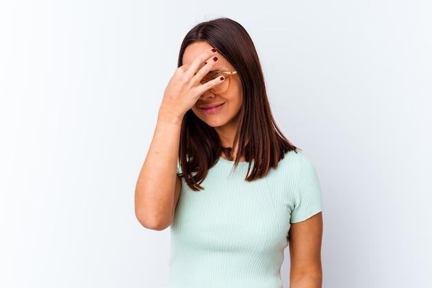 Młoda kobieta rasy mieszanej samodzielnie o ból głowy, dotykając przedniej części twarzy.