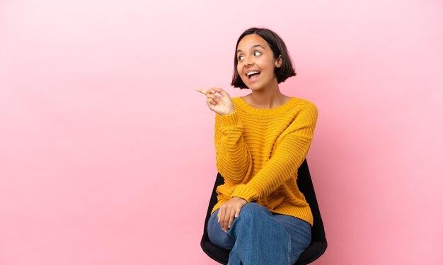 Młoda kobieta rasy mieszanej siedząca na krześle na białym tle na różowym tle, zamierzająca zrealizować rozwiązanie, podnosząc palec w górę