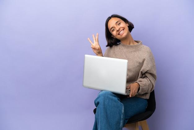 Młoda kobieta rasy mieszanej siedząca na krześle z laptopem na białym tle na fioletowym tle szczęśliwa i licząca trzy palcami