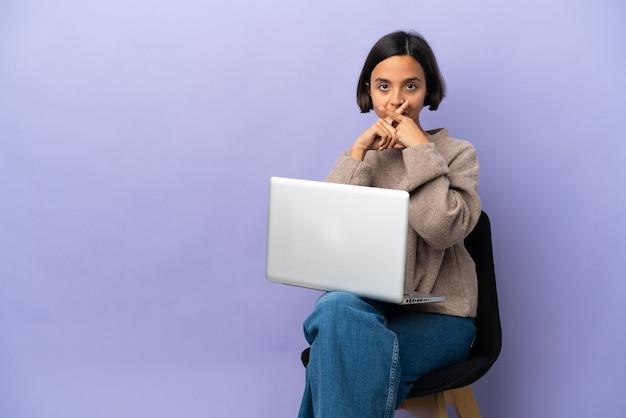 Młoda kobieta rasy mieszanej siedząca na krześle z laptopem na fioletowym tle pokazująca znak gestu ciszy