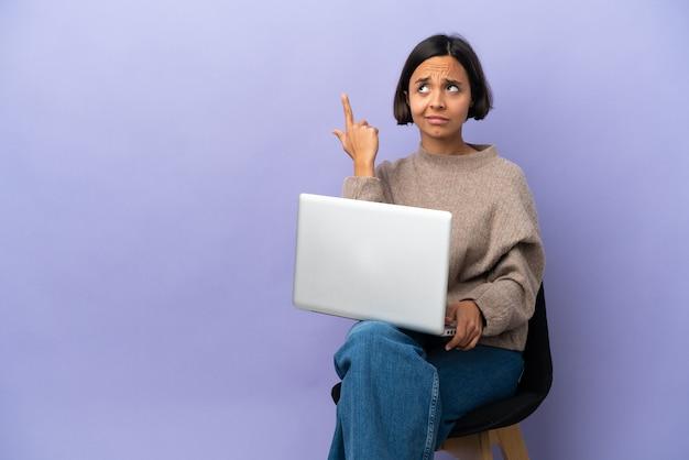 Młoda kobieta rasy mieszanej siedząca na krześle z laptopem na fioletowym tle, wykonująca gest szaleństwa, kładąca palec na głowie