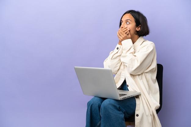 Młoda kobieta rasy mieszanej siedząca na krześle z laptopem na fioletowym tle zakrywającym usta i patrząca w bok