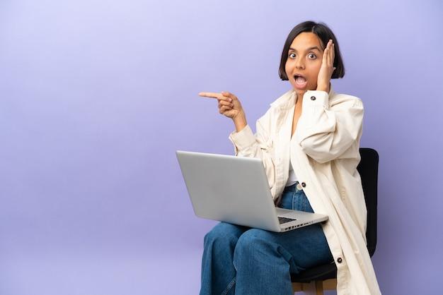 Młoda kobieta rasy mieszanej siedząca na krześle z laptopem na fioletowym tle zaskoczona i wskazująca palcem w bok