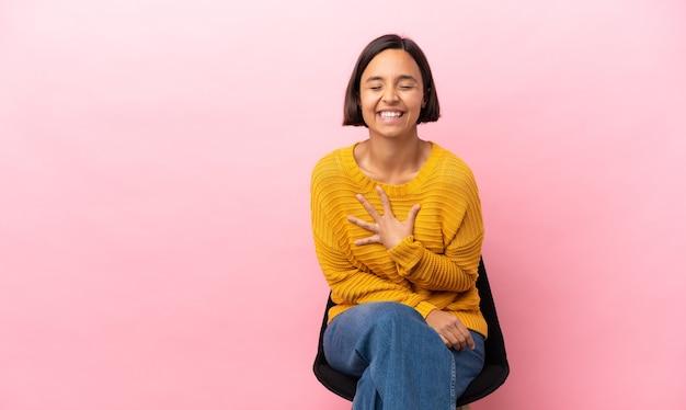 Młoda kobieta rasy mieszanej siedzi na krześle na białym tle na różowym tle dużo uśmiecha się