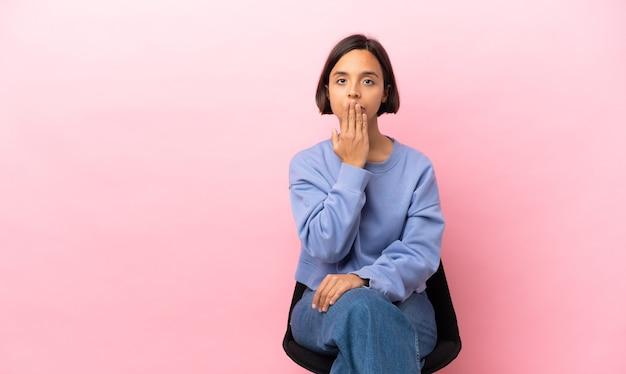 Młoda kobieta rasy mieszanej siedzi na krześle na białym tle na różowym tle obejmujące usta ręką