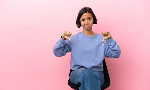 Młoda kobieta rasy mieszanej siedzi na krześle na białym tle na różowym tle pokazując kciuk w dół obiema rękami