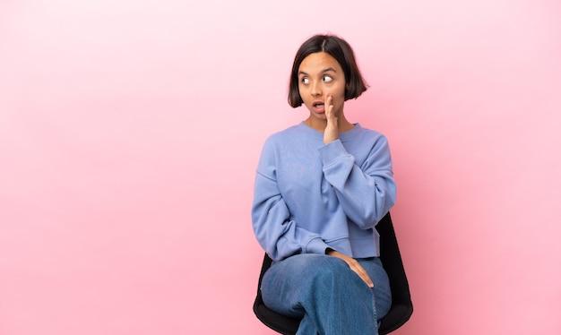 Młoda kobieta rasy mieszanej siedzi na krześle na białym tle na różowym tle, szepcząc coś z zaskoczenia gestem, patrząc w bok