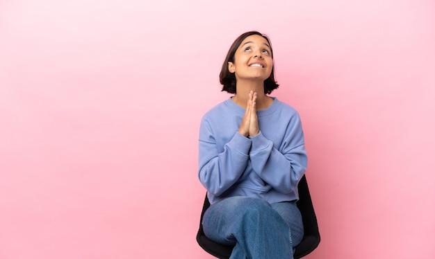 Młoda kobieta rasy mieszanej siedzi na krześle na białym tle na różowym tle trzyma dłoń razem. osoba o coś prosi