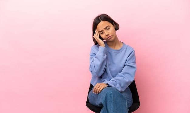 Młoda kobieta rasy mieszanej siedzi na krześle na białym tle na różowym tle z bólem głowy