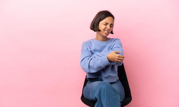 Młoda kobieta rasy mieszanej siedzi na krześle na białym tle na różowym tle z bólem łokcia