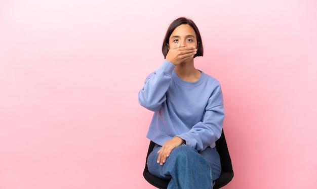 Młoda kobieta rasy mieszanej siedzi na krześle na białym tle na różowym tle zakrywając usta dłonią