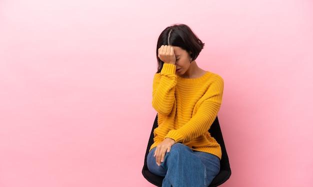 Młoda kobieta rasy mieszanej siedzi na krześle odizolowanym z bólem głowy
