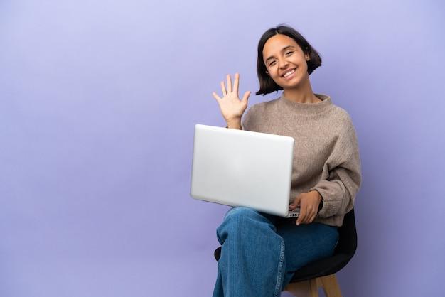 Młoda kobieta rasy mieszanej siedzi na krześle z laptopem na białym tle na fioletowym tle, licząc pięć palcami