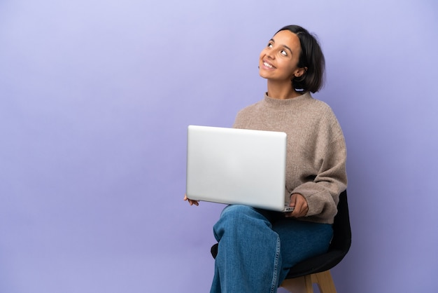 Młoda kobieta rasy mieszanej siedzi na krześle z laptopem na białym tle na fioletowym tle patrząc w górę podczas uśmiechania się