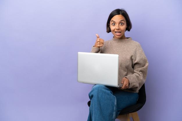 Młoda kobieta rasy mieszanej siedzi na krześle z laptopem na białym tle na fioletowym tle pokazując znak ok i gest kciuka w górę