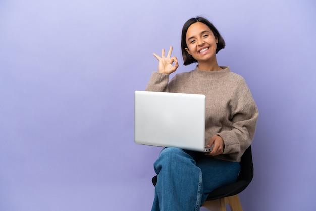 Młoda kobieta rasy mieszanej siedzi na krześle z laptopem na białym tle na fioletowym tle pokazuje znak ok palcami
