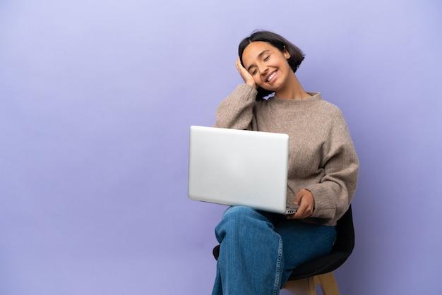 Młoda kobieta rasy mieszanej siedzi na krześle z laptopem na białym tle na fioletowym tle śmiejąc się