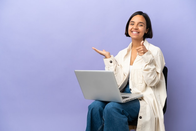 Młoda kobieta rasy mieszanej siedzi na krześle z laptopem na białym tle na fioletowym tle, trzymając wyimaginowaną copyspace na dłoni, aby wstawić reklamę i kciuki w górę