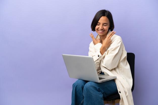 Młoda kobieta rasy mieszanej siedzi na krześle z laptopem na białym tle na fioletowym tle, uśmiechając się i pokazując znak zwycięstwa