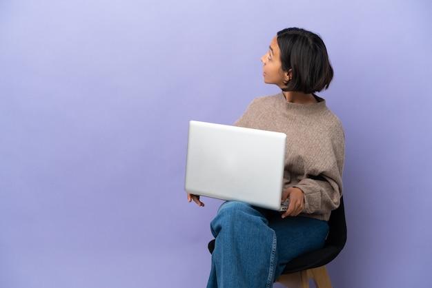 Młoda kobieta rasy mieszanej siedzi na krześle z laptopem na białym tle na fioletowym tle w pozycji tylnej i patrząc wstecz
