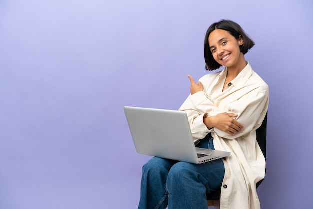 Młoda kobieta rasy mieszanej siedzi na krześle z laptopem na białym tle na fioletowym tle, wskazując do tyłu