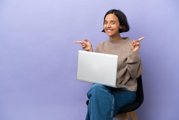 Młoda kobieta rasy mieszanej siedzi na krześle z laptopem na białym tle na fioletowym tle, wskazując palcem po bokach i szczęśliwa