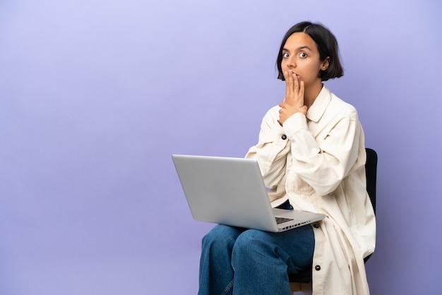 Młoda kobieta rasy mieszanej siedzi na krześle z laptopem na białym tle na fioletowym tle zakrywając usta dłonią