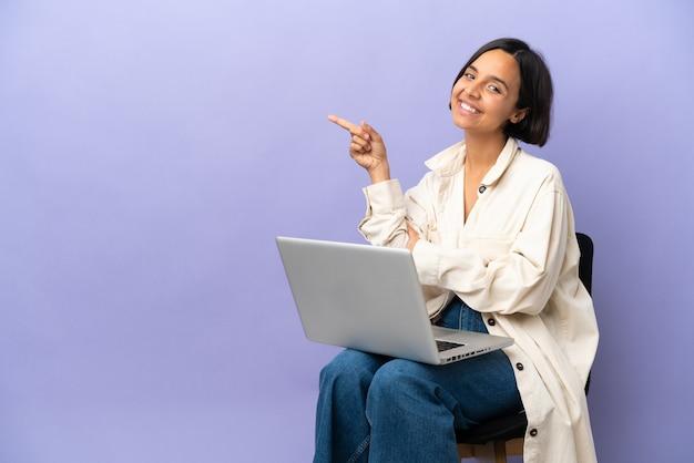 Młoda kobieta rasy mieszanej siedzi na krześle z laptopem na białym tle, wskazując palcem na bok