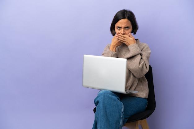 Młoda kobieta rasy mieszanej siedzi na krześle z laptopem na białym tle zakrywając usta rękami