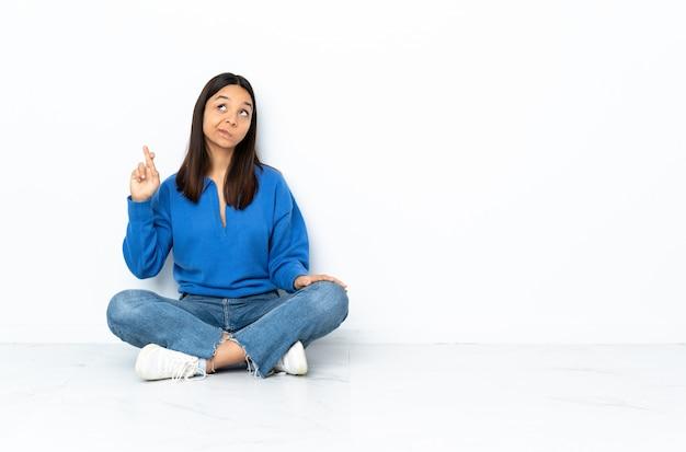 Młoda kobieta rasy mieszanej siedzi na podłodze na białej ścianie z palcami skrzyżowanymi i życząc jak najlepiej