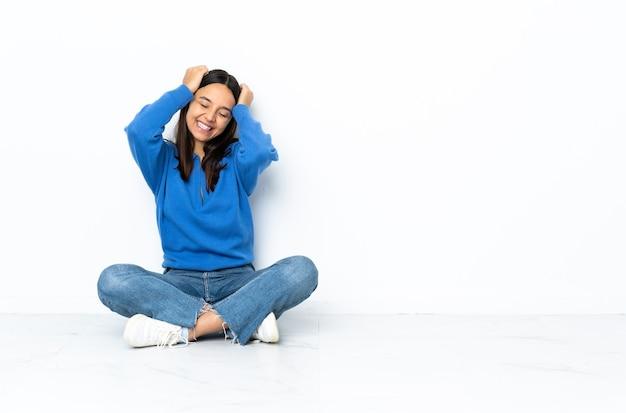Młoda kobieta rasy mieszanej siedzi na podłodze na białym śmiejąc się