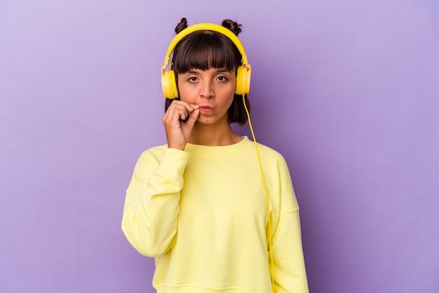 Młoda kobieta rasy mieszanej słuchania muzyki na białym tle na fioletowym tle z palcami na ustach zachowując tajemnicę.