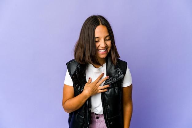 Młoda kobieta rasy mieszanej, śmiejąc się, trzymając ręce na sercu, pojęcie szczęścia.