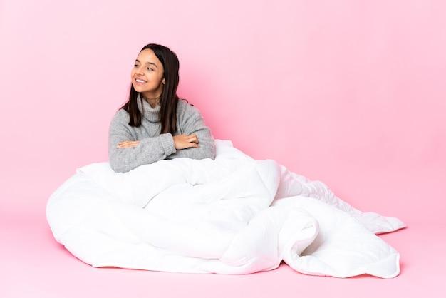 Młoda kobieta rasy mieszanej sobie pijama siedzi na podłodze z rękami skrzyżowanymi i szczęśliwa