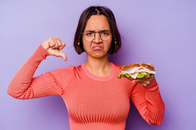 Młoda kobieta rasy mieszanej trzyma kanapkę na białym tle na fioletowym tle pokazując gest niechęci, kciuk w dół. koncepcja niezgody.