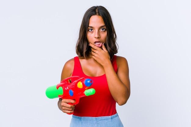 Młoda kobieta rasy mieszanej trzyma pistolet na wodę na białym tle trzyma miejsce na dłoni, trzymaj rękę nad policzkiem. zdumiony i zachwycony.