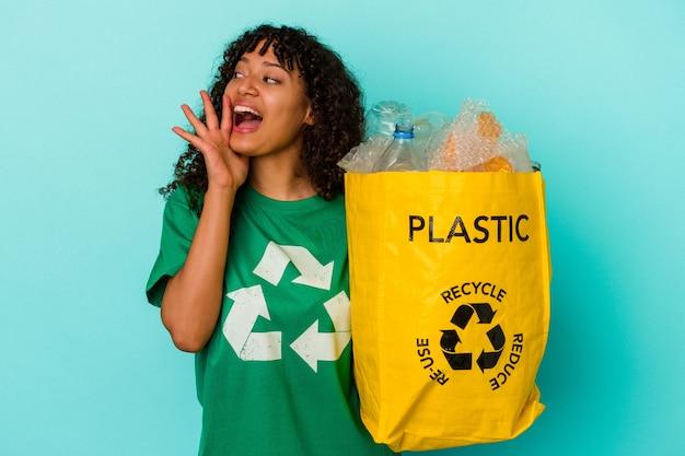 Młoda kobieta rasy mieszanej trzyma plastikową torbę z recyklingu na białym tle na niebieskim tle krzycząc i trzymając dłoń w pobliżu otwartych ust.