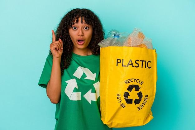 Młoda kobieta rasy mieszanej trzyma plastikową torbę z recyklingu na białym tle na niebieskim tle, mając pomysł, koncepcję inspiracji.