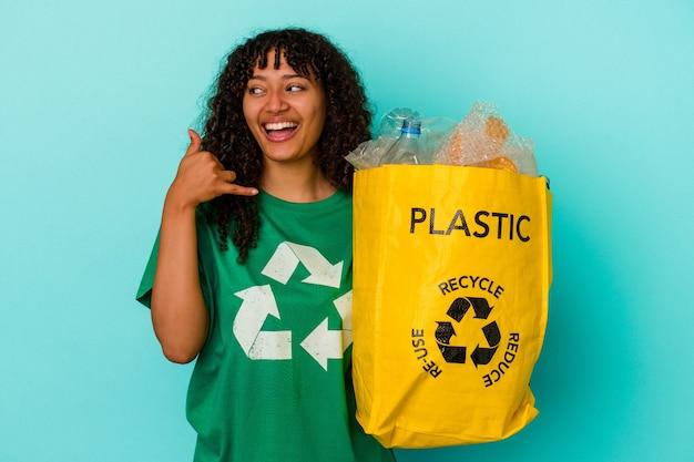 Młoda kobieta rasy mieszanej trzyma plastikową torbę z recyklingu na białym tle na niebieskim tle pokazując gest połączenia z telefonem komórkowym palcami.