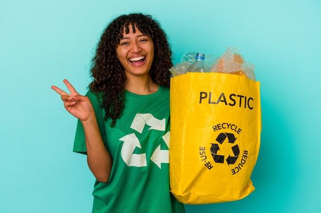 Młoda kobieta rasy mieszanej trzyma plastikową torbę z recyklingu na białym tle na niebieskim tle radosna i beztroska pokazująca palcami symbol pokoju.
